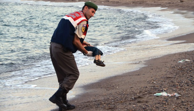 A paramilitary police officer carries the lifeless body of a migrant child after a number of migrants died and a smaller number were reported missing after boats carrying them to the Greek island of Kos capsized, near the Turkish resort of Bodrum early Wednesday, Sept. 2, 2015. (AP Photo/DHA) TURKEY OUT/ANK801/306567499844/TURKEY OUT/1509021754