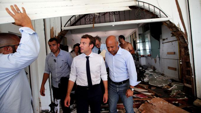 France's President Emmanuel Macron looks on in destroyed building during his visit to the French Caribbean island of St. Martin